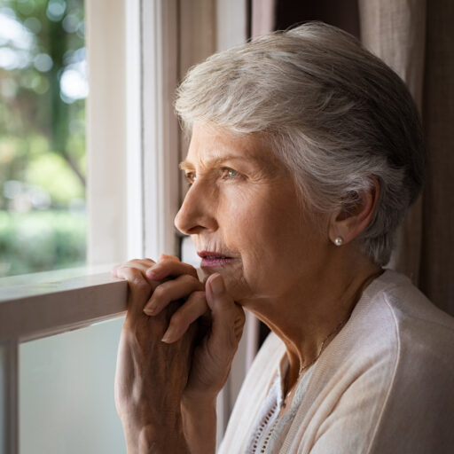 A senior woman, who is experiencing signs of depression, looks out the window.