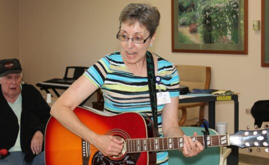 Therapist provides music therapy in a senior community
