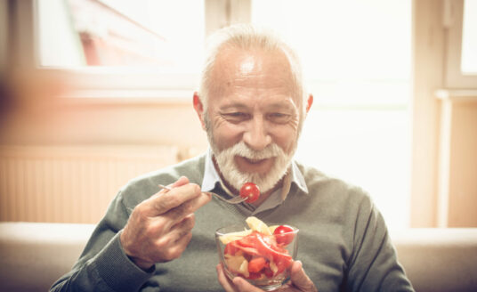 Senior man enjoying a summer snack, as he's finding ways for healthy aging