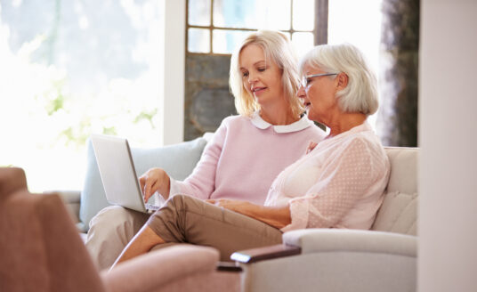 Adult daughter helping senior mother with computer in preparation for touring an assisted living community