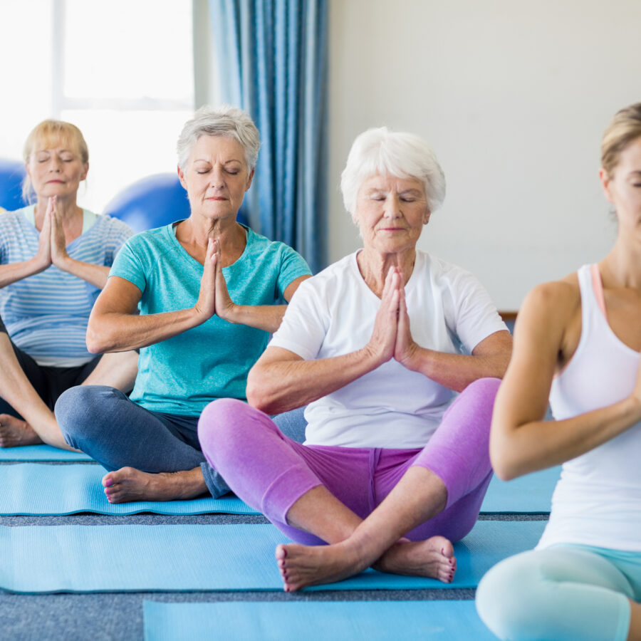 A group of seniors practicing yoga. The benefits of yoga for seniors range from improved health, reduced stress, and making new friends.