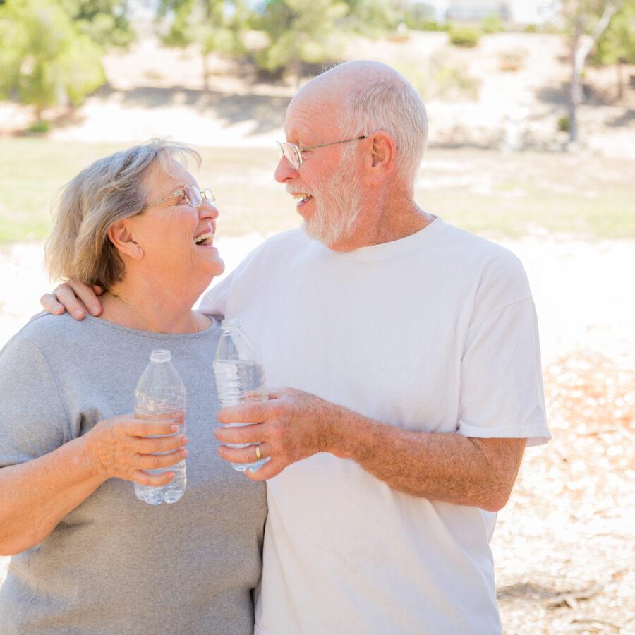 A senior couple staying hydrated in the summer, with their water bottles in-hand.