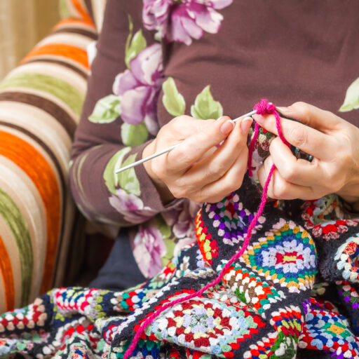 Senior woman plays with fidget blanket, which can be a tool to ease the nerves of seniors with dementia and anxiety.