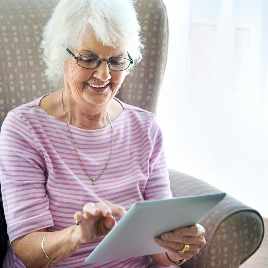 Technology helps seniors stay in touch with loved ones - no matter where they live! This senior woman uses a tablet to connect with her family.