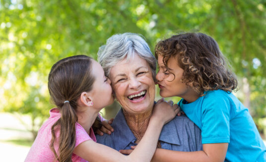 Celebrating Grandparents Day at Bethesda give seniors a chance to visit with their families. Here, a senior woman hugs her granddaughters.