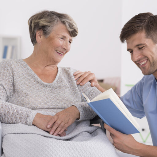 A volunteer at a skilled nursing home community reads to a senior woman.