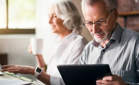 An older couple uses their devices. This technology helps seniors age in place.