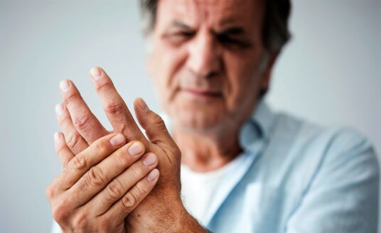 Senior man holds his hand, as he's suffering from arthritis pain. Read these tips from Bethesda to manage arthritis pain during the winter months.