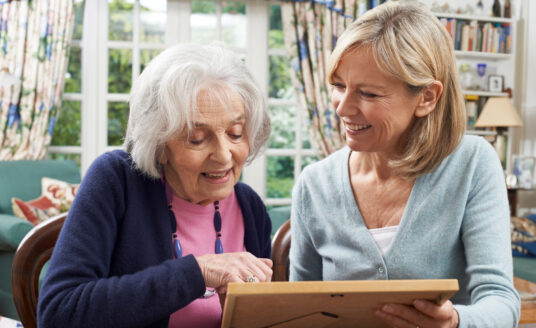 Senior woman looking at photos with her daughter. It can be confusing knowing when the right time to make the transition from Assisted Living to Memory Care, but knowing the signs of memory loss can help.