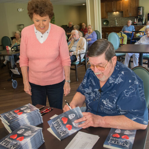 Al Becherer, a Bethesda Terrace resident, signs copies of his published book for his neighbors and fellow residents.