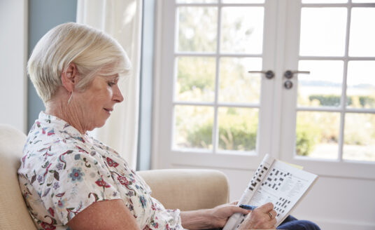Senior woman doing a crossword puzzle, which is an activity known to promote memory health