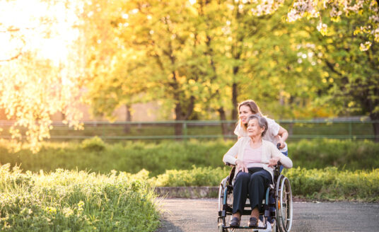 Myths about hospice care can cause negative assumptions. In fact, hospice care is more about improving or maintaining quality of life. Here, a woman walks with her elderly parent, celebrating the little things.