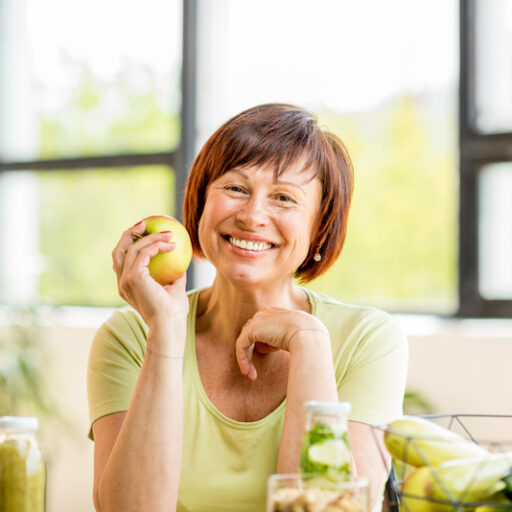 As you age, it's important to understand the importance of geriatric nutrition. Here, a senior woman eats an apple.