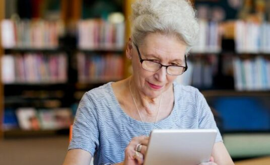 A senior using a tablet at the library.