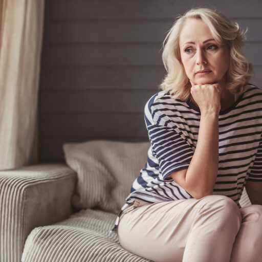 An adult woman with a contemplative look, because she feels guilt for moving a parent into a senior care community.