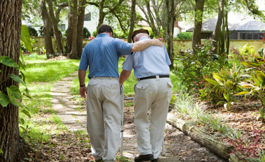 A an adult son walks with his father down a path. There are many sacrifices family caregivers make to ensure that their loved ones receive the care they need—including finances and personal well-being.