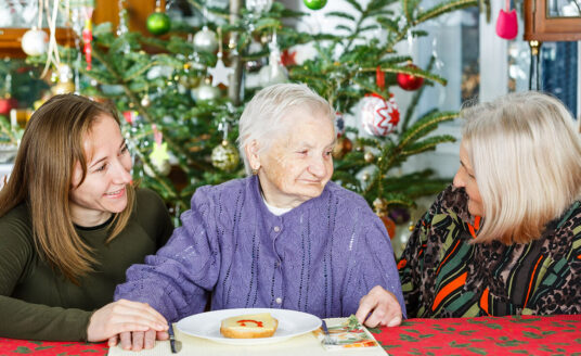 Two daughters celebrate the holidays at an assisted living community with their mother.