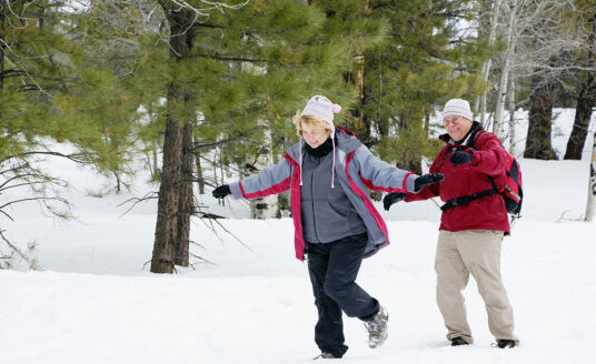 A senior couple takes a relaxing stroll in the snow. Taking time for yourself will help you avoid holiday stress.