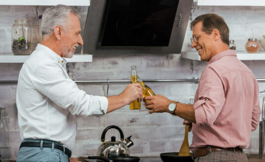 Two older adult men cheers, as this little get together offers respite for a senior caregiver, to ease a caregiver's burden.