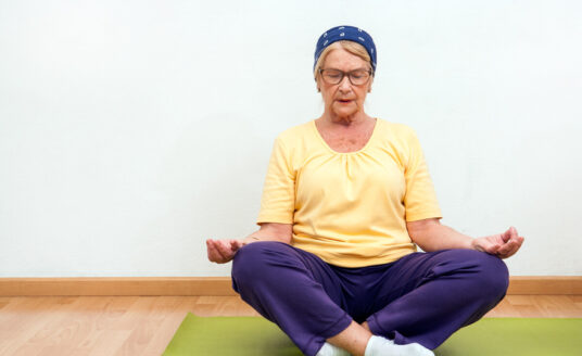 A senior woman meditates. The benefits of mindfulness meditation for seniors include stress relief and patience.