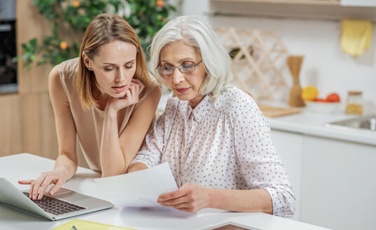 An adult woman and her senior mother look over materials when choosing an assisted living community.
