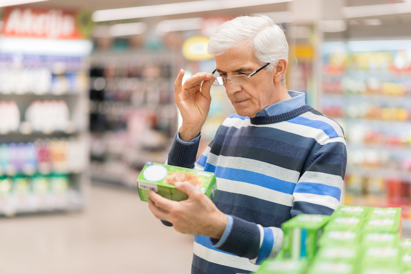 A senior man in a grocery store reads a nutrition label. Getting the most nutritious foods, with fewer calories, is an important part of weight loss for seniors.
