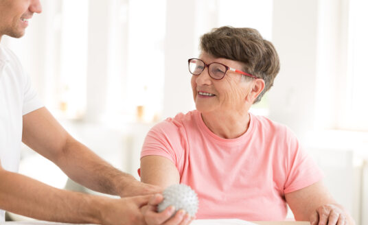 A senior woman uses rehab services, aiding in recovery after a stroke