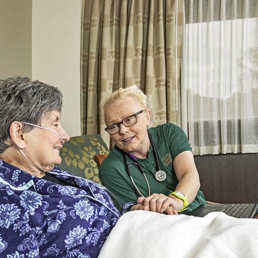 A nurse explains to a senior woman what hospice care does