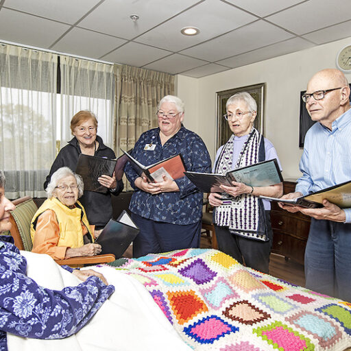 A group of volunteers sings to a senior woman because music touches lives of dying people.