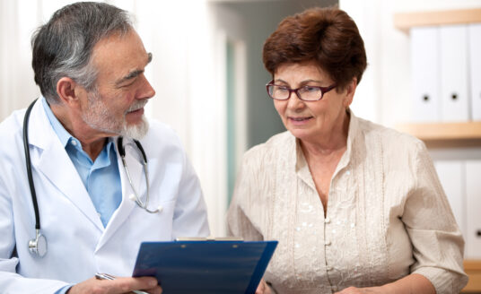 After she prepared for her doctor's appointment, a senior woman sits with her doctor to review her records.