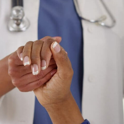 A doctor holds a patient's hand and practices age-friendly health care