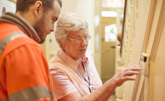A man helps a senior woman with senior home safety