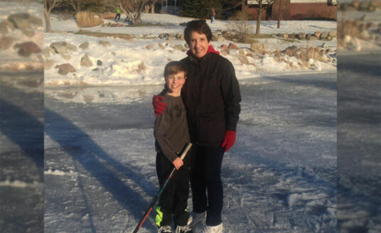 A grandmother ice skates to play with grandchildren