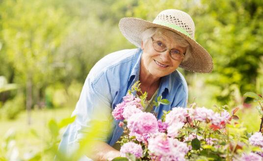 A senior woman plants flowers in her senior-friendly garden