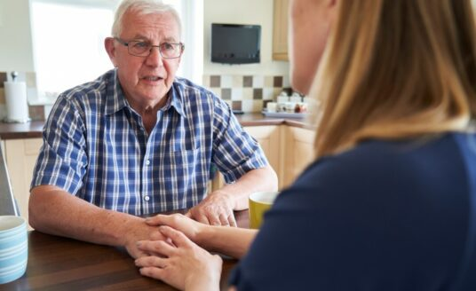 A woman talks to her senior father about dementia.