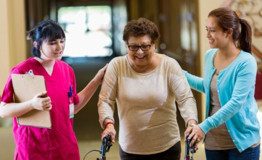 A Care Manager walks with a senior woman and her daughter. Providing a complete geriatric assessment is only one of the ways a care manager can help a family caregiver.