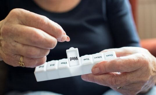 A senior woman using her pillbox, which has been organized with the help of medication therapy management (or MTM)