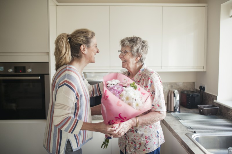 An older adult woman greets her senior mother, who is living with Alzheimer's, with a bouquet of flowers.