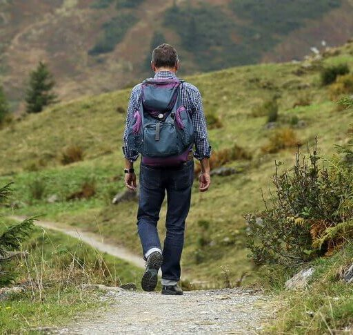 A man walks down a path, as spending time in nature is helping him move forward after his loved one died.