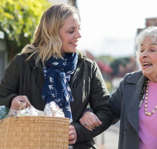 An adult woman carries groceries for a senior woman, as she knows that kindness makes you healther.