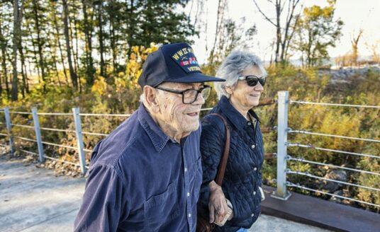 A senior Veteran and his wife walk along a trail at their senior living community.