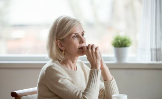An adult woman contemplates her decision, as she may be feeling caregiver guilt after moving a parent into senior living.
