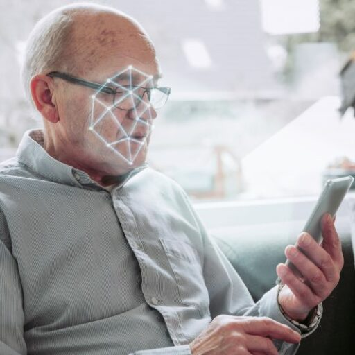 There is a lot of research about AI and aging happening now. Here, a man holds up his smart phone as it scans his face.