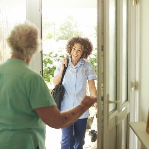 A caregiver meets a senior woman at her front door for in-home respite care services.
