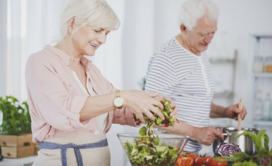 An older adult couple prepares a healthy meal at home, to better manage diabetes