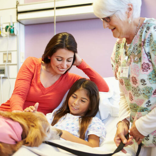 If you're looking for a meaningful retirement, try volunteering at a children's hospital. Here, a senior woman volunteers and visits with a child and her mother.