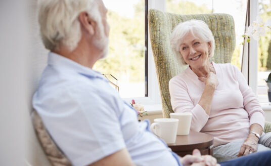 A senior couple living in a retirement community sits and chats in their personal apartment.