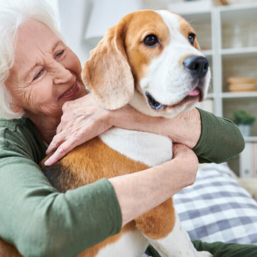 A senior woman hugs her dog. Keeping your pet as you age is proven to make us happier and healthier.