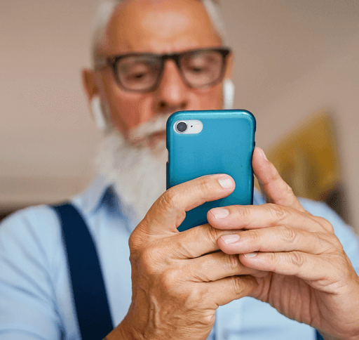 A senior man looks at hearing aid apps on his smart phone.