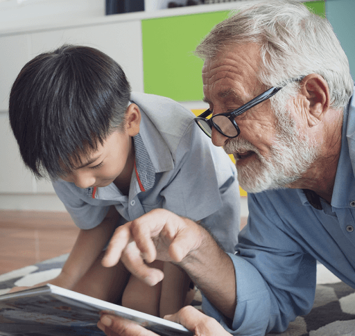 A senior man reads with a young boy.